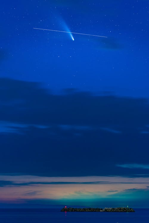 Long exposure of small glowing stars in vivid blue pink evening sky over island in endless ocean