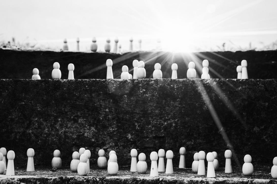 Black and white heap of wooden figurines placed on stairs illustrating social mobility and hierarchy on street with bright sunlight
