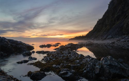 Rough stones located in calm clean water of sea against cloudy sundown sky