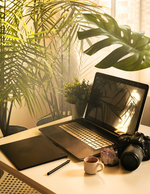 Black and Silver Laptop Computer Beside Black Dslr Camera on Brown Wooden Table