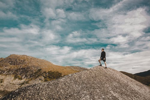 Man in Black Jacket Standing on Gray Rock Under White Clouds and Blue Sky
