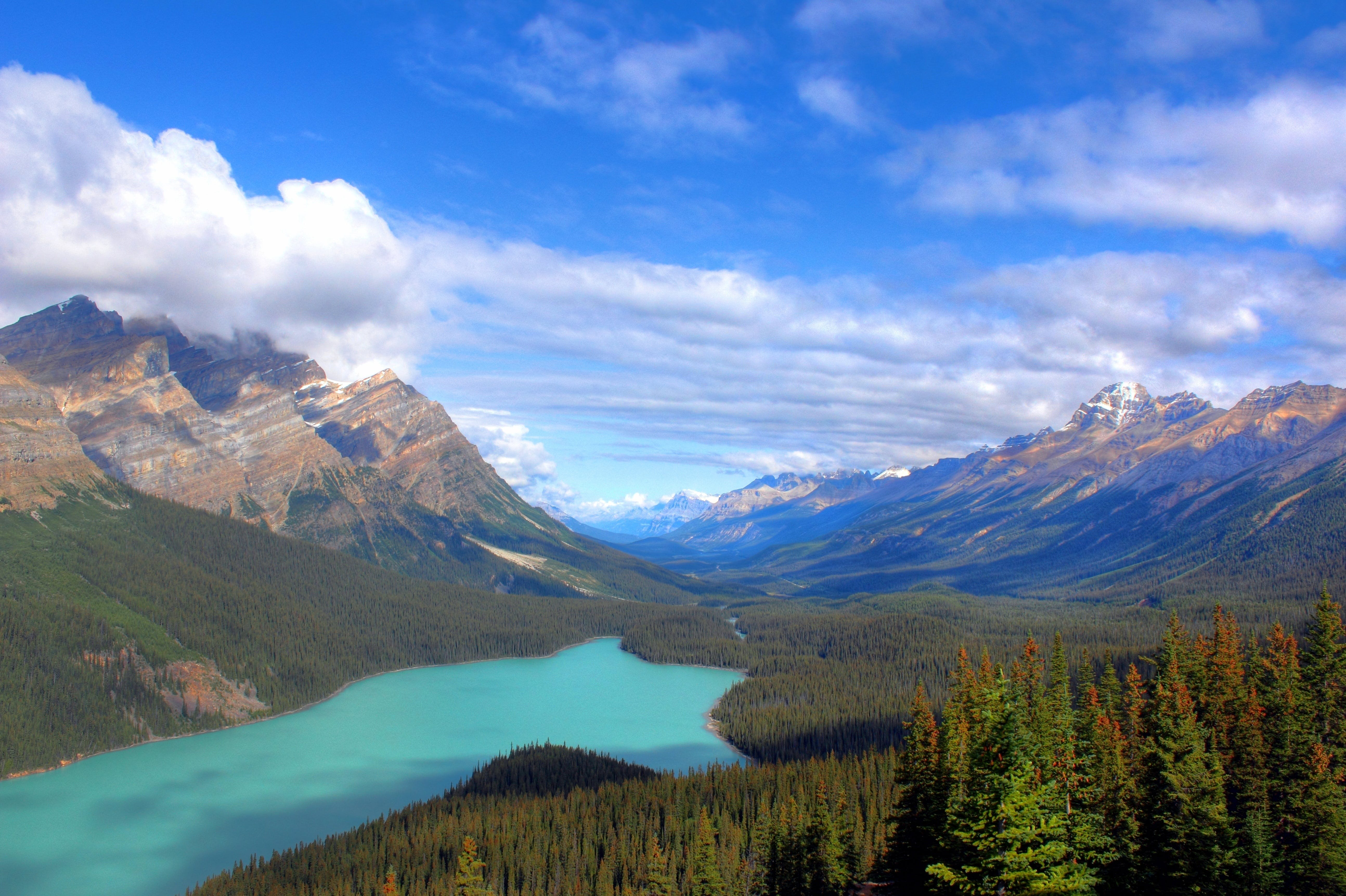 Blue Lake Near Mountains Under Blue and White Sunny Cloudy Sky