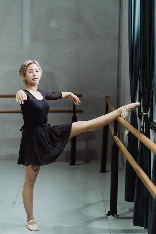 Ethnic ballerina stretching leg on barre in studio