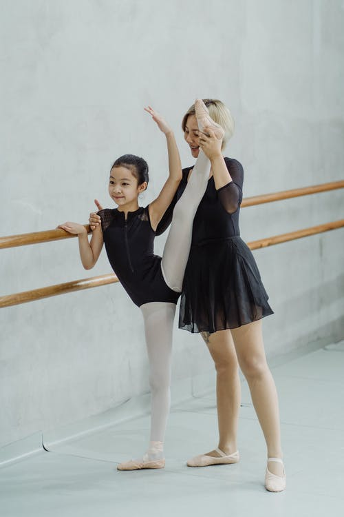 Full body of positive young ethnic female ballet instructor helping little girl to do stretching exercise near barre during training in studio