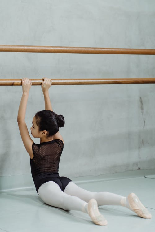 Anonymous little ethnic female dancer stretching back while doing barre exercise in studio