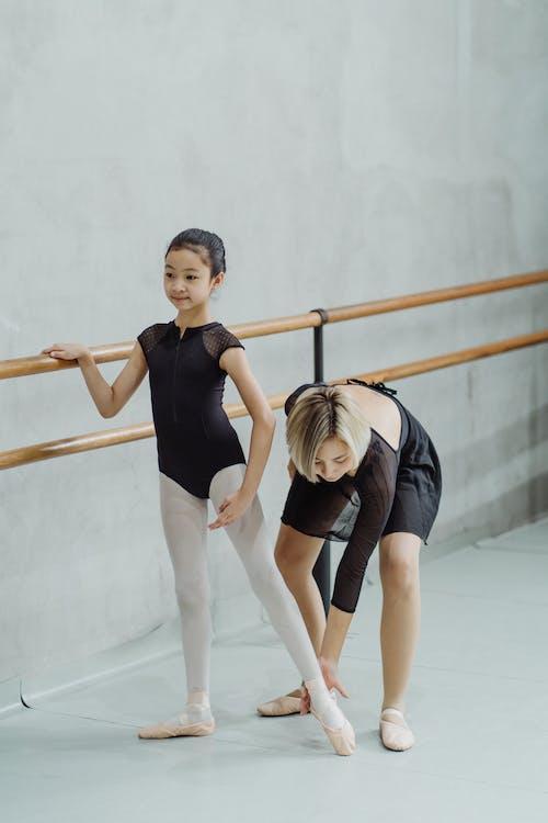 Full body of professional ballerina correcting foot position of little ethnic female dancer standing near barre during rehearsal