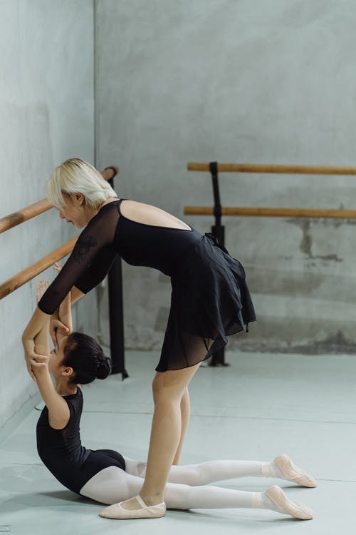 Young female instructor helping little ethnic ballerina to stretch back during training