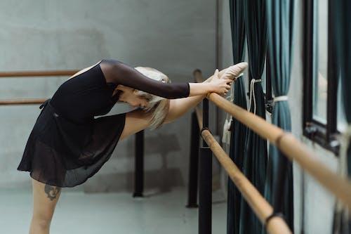 Giovane Ballerina Femminile Flessibile Che Allunga Le Gambe Vicino Alla Sbarra In Studio