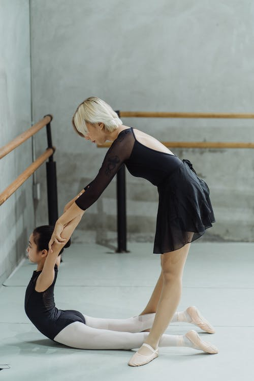 Anonymous ballet master helping ethnic beginner girl to increase back flexibility during training