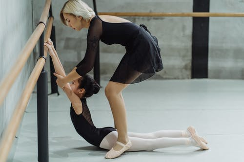 Side view of concentrated young Asian female dancer with blond hair supporting arms of little ethnic ballerina holding barre during stretching exercise
