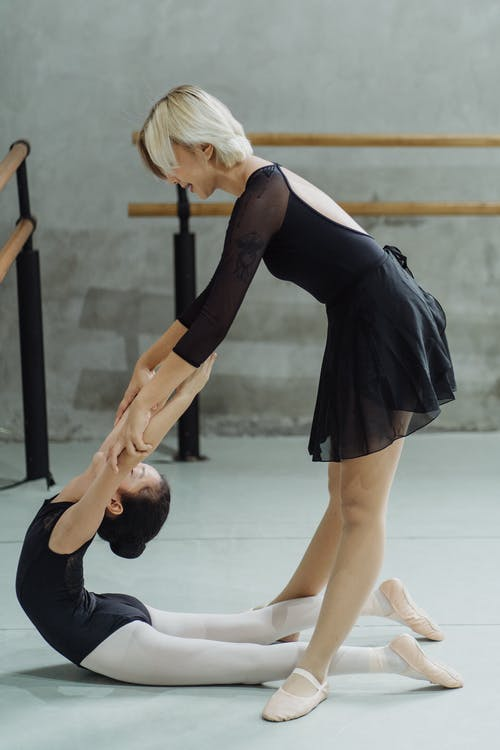 Young female instructor helping little ballerina to improve back flexibility in studio