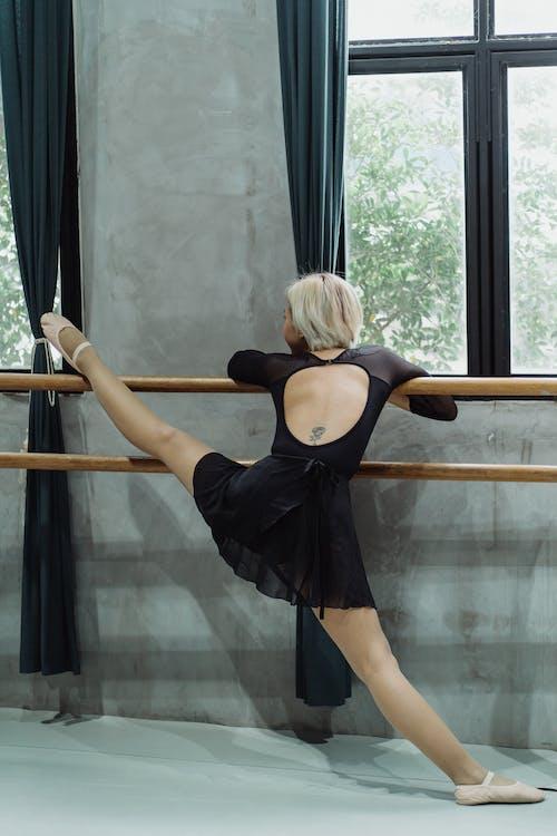Ballerina In Forma Anonima Facendo Esercizio Di Stretching Sulla Sbarra In Studio