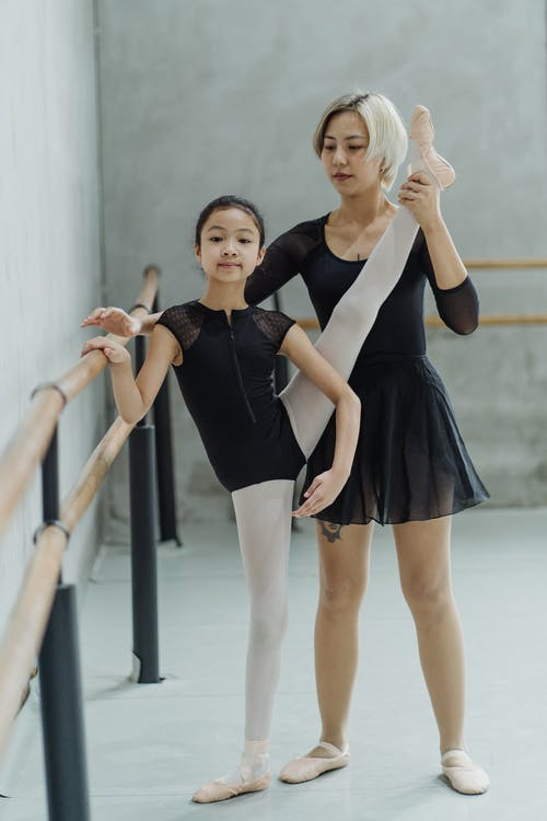 Full body of positive little ethnic girl in pointe shoes and bodysuit standing near barre and performing Developpe ballet pose with help of Asian female instructor