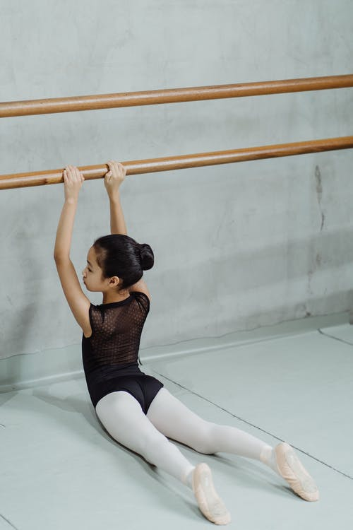 Graceful little ballerina stretching back while doing barre exercise in light studio