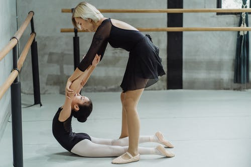 Side view of young ethnic female ballet master helping little girl doing backbend exercise during training in studio