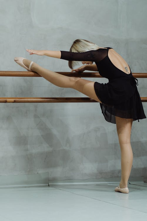 Anonymous ballerina warming up on barre in studio