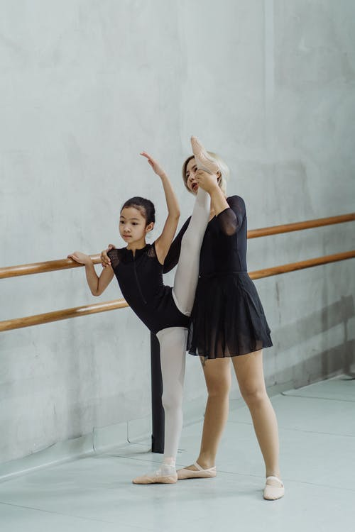 Full length of young Asian female ballet teacher supporting leg of beginner girl in leotard and pointe shoes standing in Developpe position near barre in studio