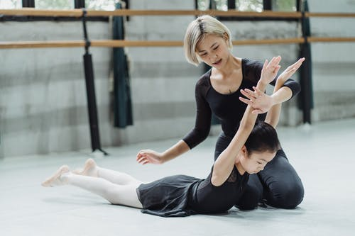 Concentrated ethnic child stretching back during training in studio with young Asian female ballet instructor