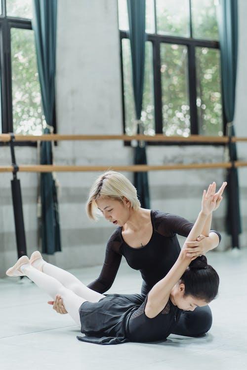 Concentrato Piccola Ballerina Etnica Facendo Esercizio Backbend Con Il Giovane Istruttore Femminile Asiatico In Studio