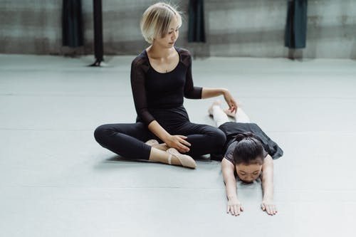 Full body of little Asian ballerina lying on floor with closed eyes after training in studio with young female ethnic instructor