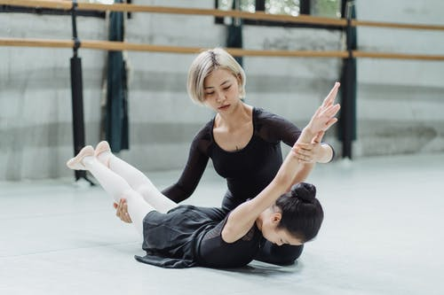 Young professional dancer helping Asian girl stretching back during ballet exercise in dancing hall