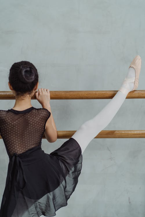 Unrecognizable girl stretching leg on barre during ballet class