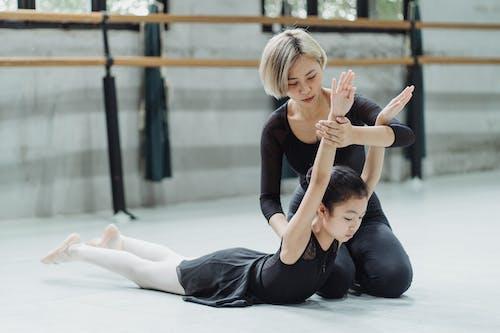 Insegnante Di Balletto Etnico Che Sostiene La Ragazza Durante L'esecuzione Dell'esercizio Di Balletto