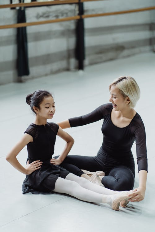 Content Asian teacher with pupil during ballet class in hall