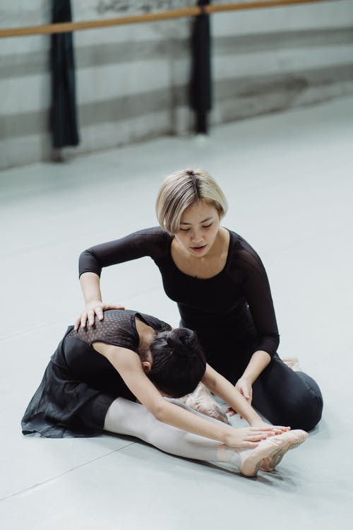 Anonymous girl leaning forward while stretching legs near female teacher during ballet workout in hall