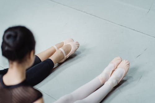 Faceless trainer teaching girl while performing ballet exercise