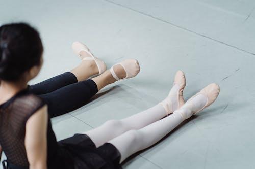 Crop ballet teacher with girl exercising on floor