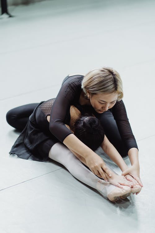 From above of young Asian instructor stretching back of unrecognizable girl in uniform while practicing ballet on floor