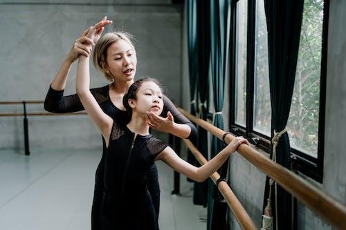 亞洲芭蕾舞教練向女孩解釋技術