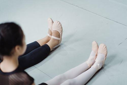Crop ballerinas in ballet slippers sitting on floor in studio
