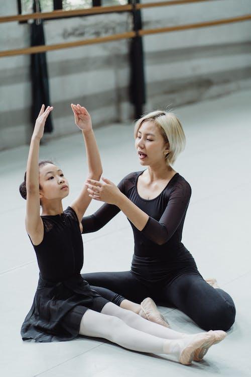 亞洲芭蕾舞教練和女孩練習地板上的動作