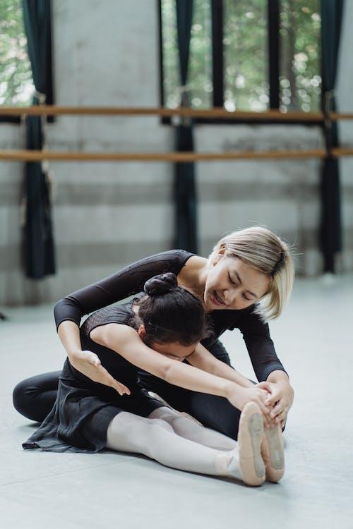 積極的亞洲芭蕾舞老師幫助女孩實習生伸展身體