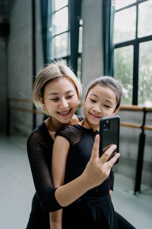 Cheerful Asian ballerinas taking selfie in ballet studio