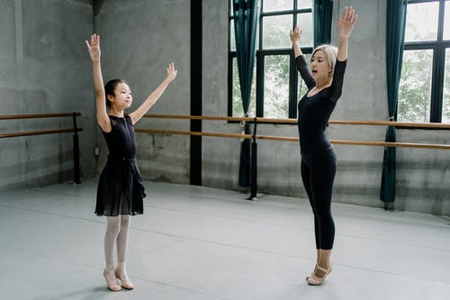 Full body professional female ballet instructor in leotard and girl ballerina standing on tiptoes and raising arms graciously in spacious light ballet studio