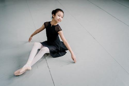 Smiling Asian girl ballerina sitting gracefully on floor in studio