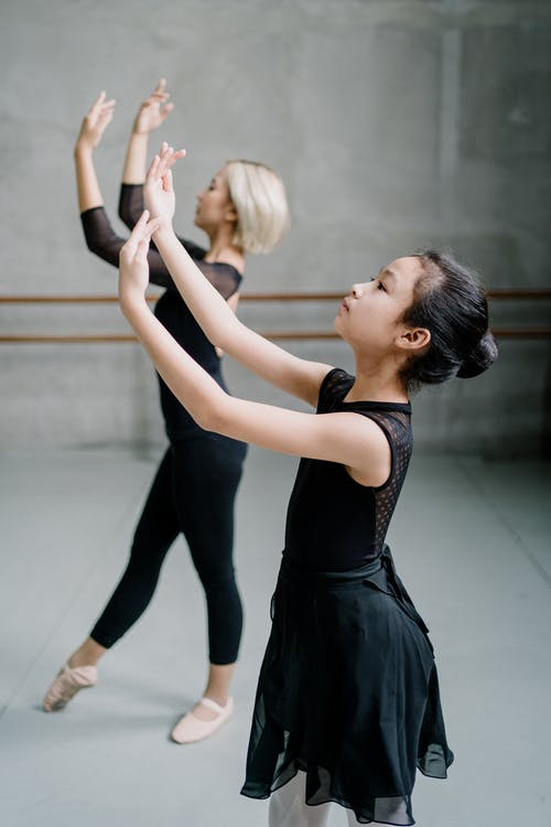 Side view Asian woman and girl ballerinas in black wear dancing ballet with arms raised in spacious light studio