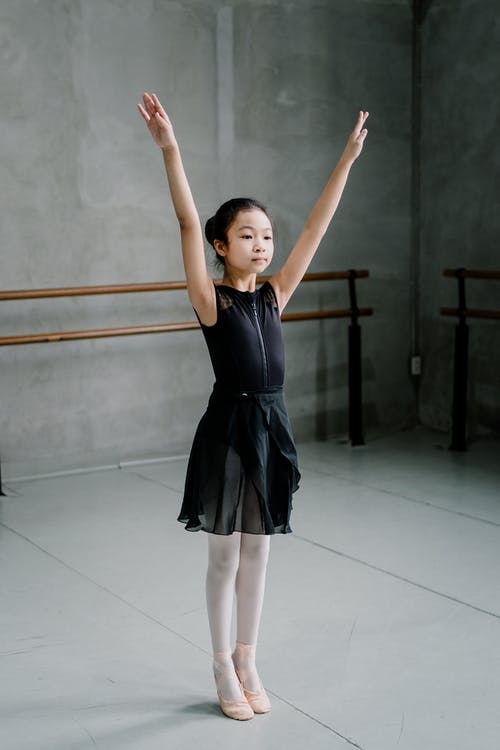 Asian girl ballerina standing with arms raised in studio
