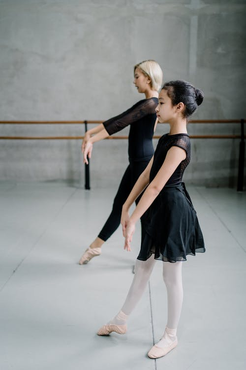Side view full body ballerina girl copying movements of female ballet instructor during class in ballet studio