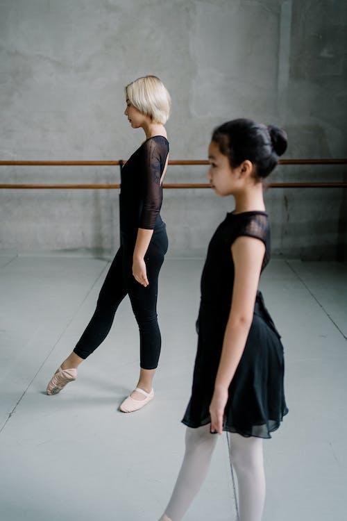 Asian ballerinas practicing movements in studio