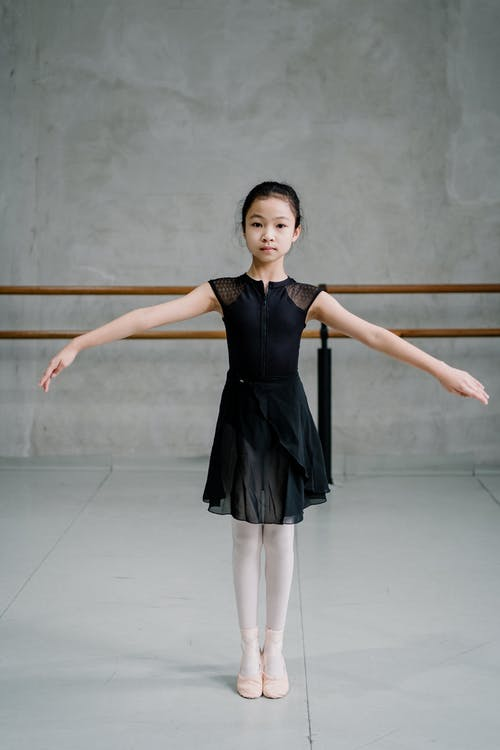 Full body calm Asian girl ballerina standing with arms outstretched in light ballet studio and looking at camera