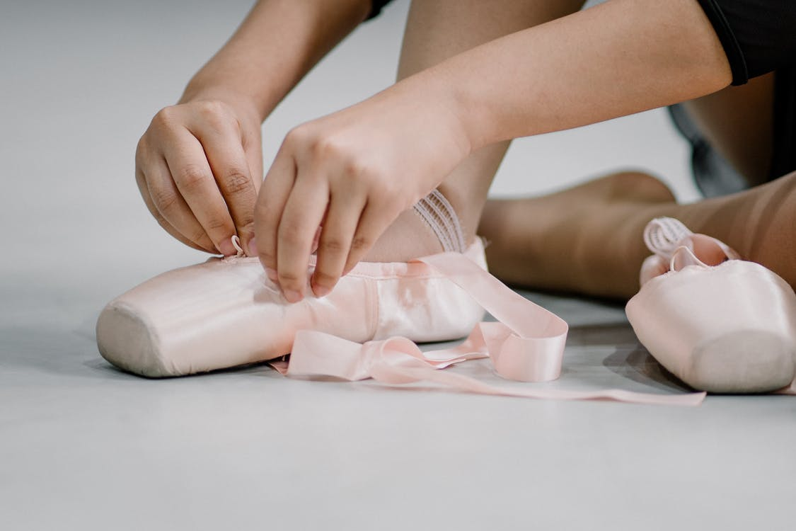 Crop faceless ballerina girl tying straps of pointe shoes