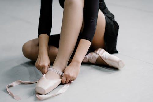 Crop unrecognizable ballerina lacing pointe shoes