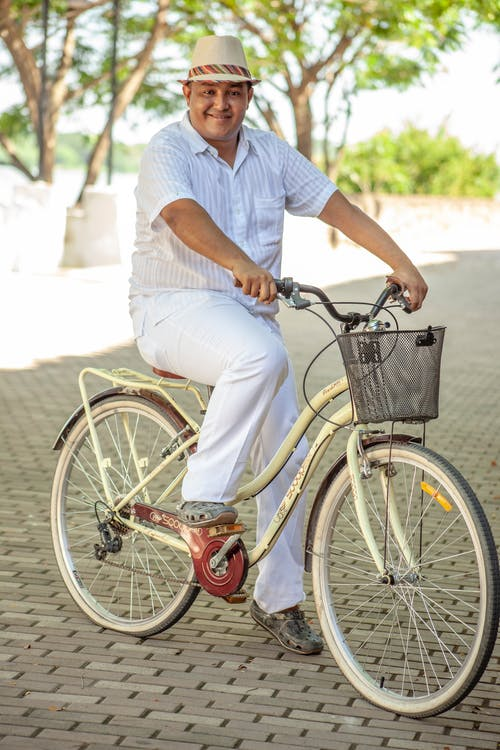 Man in White T-shirt and Blue Denim Jeans Riding on Bicycle