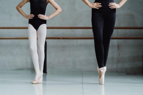 Crop unrecognizable ballerinas in leotards standing on tiptoes with hands on waist while practicing dance movements in light studio