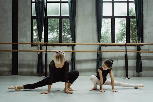 Asian ballerinas stretching legs on floor in spacious studio