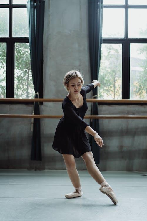 Charming Asian ballerina performing dance in studio